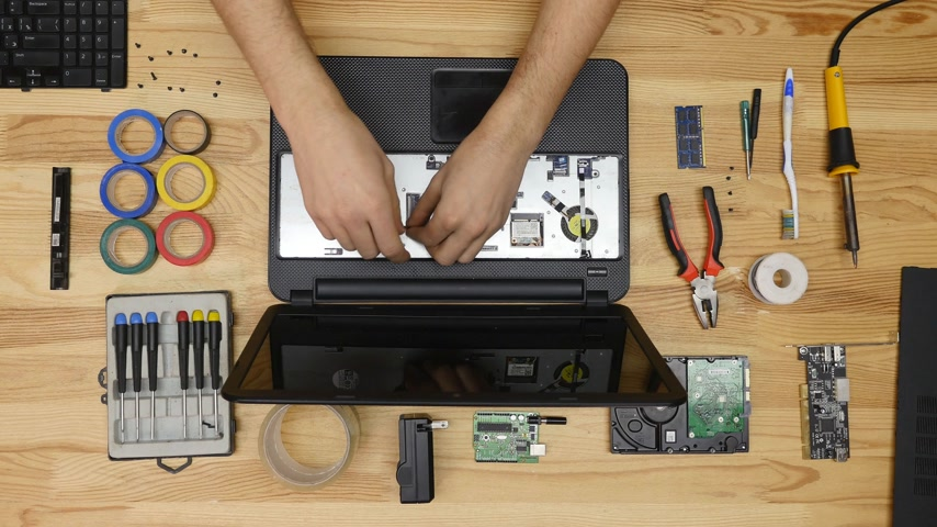 inventing : A man disassemble a laptop with a screwdriver. Wooden table top view.