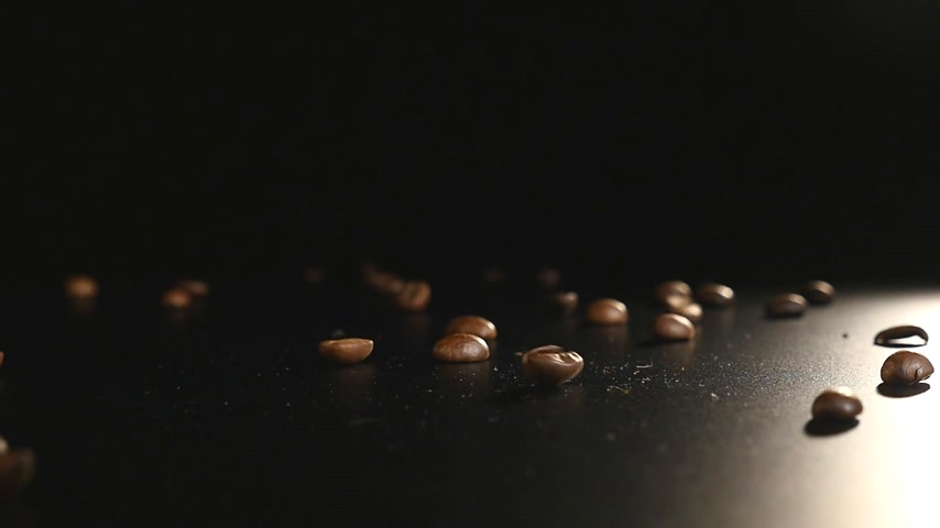 wipe away : Coffee Beans - Falling. A 96 FpS macro shot of coffee beans falling on black surface. A beautiful generic shot for any coffee related themes or title backgrounds