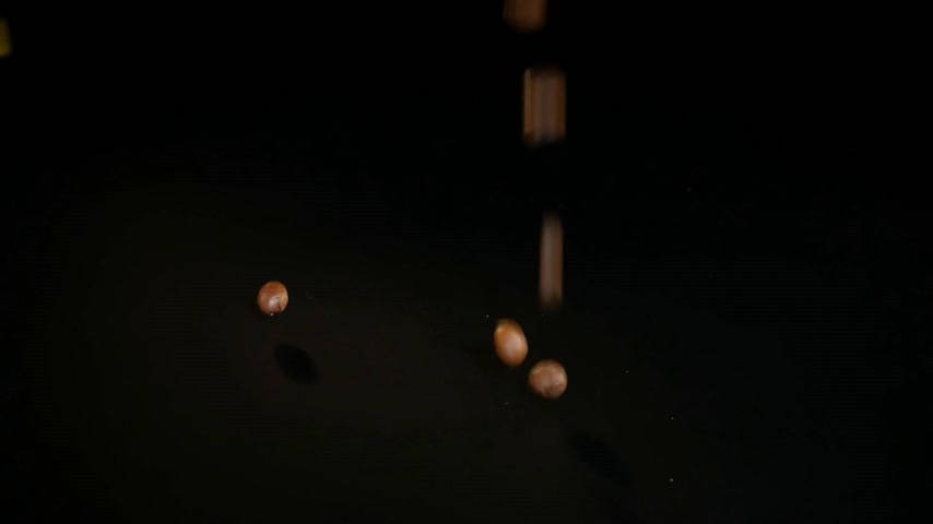 ristretto : Coffee Beans - Falling. A 96 FpS macro shot of coffee beans falling on black surface. A beautiful generic shot for any coffee related themes or title backgrounds