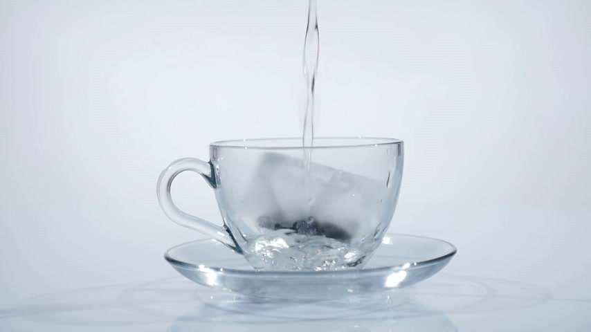 tea bag : Tea bag in a glass cup being filled with hot water to make tea. Slow motion Stock Footage