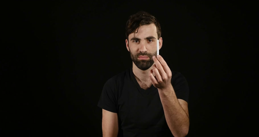 carcinogenic : man deciding between electronic or normal cigarette on black background Stock Footage