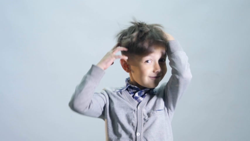 unbalanced : The boy ruffles the his hair on grey background