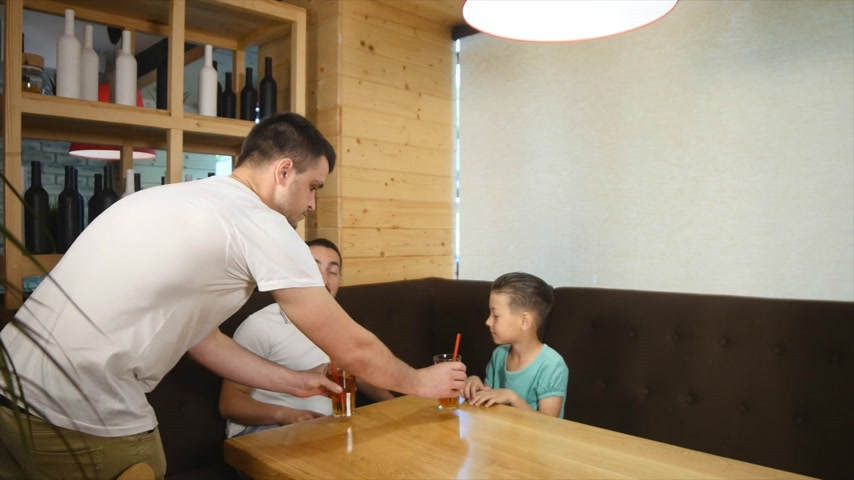 healthyfood : Father and little son sitting in cafe with juice and drinking