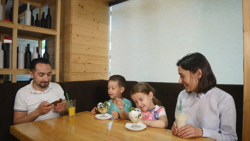 littlegirl : Happy little girl and boy eating ice cream in cafe and father photographed there Stock Footage