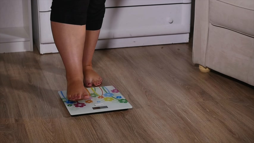paunchy : fat woman stands on the scales and starts to rejoice