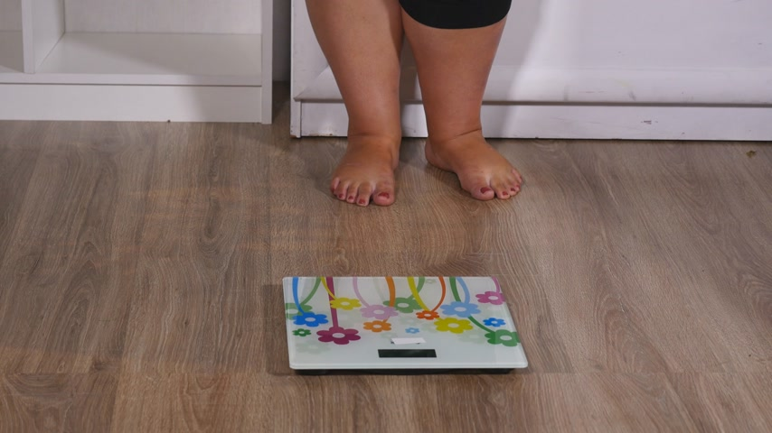 paunchy : fat woman stands on the scales and starts to rejoice, shows class