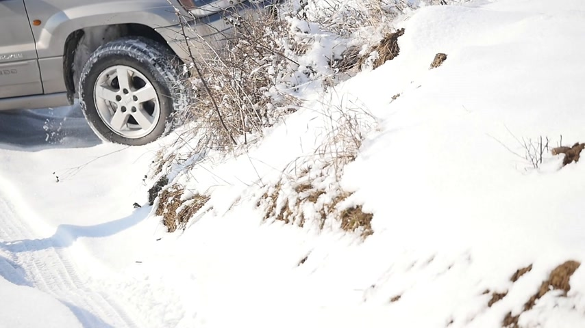 escorregadio : 21.01.2018, Chernivtsi, Ukraine - Suv with snowy wheels and winter tires driving on snow, close-up view