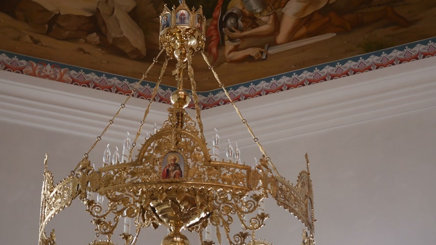 enforcamento : 30.01.2018, Chernivtsi, Ukraine - Chandelier in the Church. Candles Are Lit on the Chandelier in the Orthodox Church. in the Background, a Large Iconostasis Stock Footage