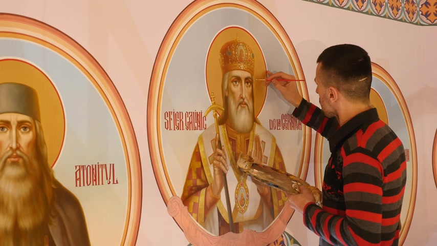 chrześcijaństwo : 30.01.2018, Chernivtsi, Ukraine - Male Artist is Standing and painting the Icon of Orthodox Saint , Holding a Palette With Paints
