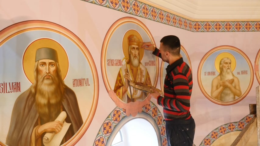 festett : 30.01.2018, Chernivtsi, Ukraine - Male Artist is Standing and painting the Icon of Orthodox Saint , Holding a Palette With Paints