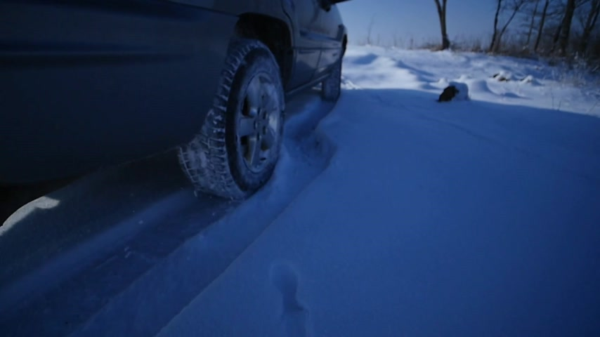 preso : Suv with snowy wheels and winter tires driving on snow, close-up view