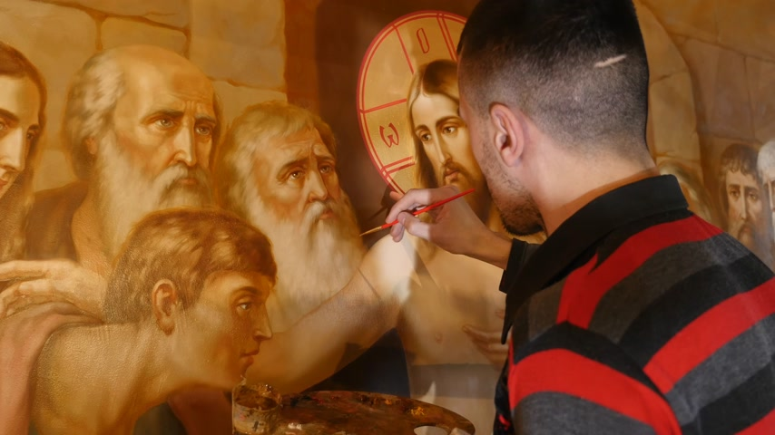 Male Artist is Standing and painting the Icon of Orthodox Saint , Holding a Palette With Paints