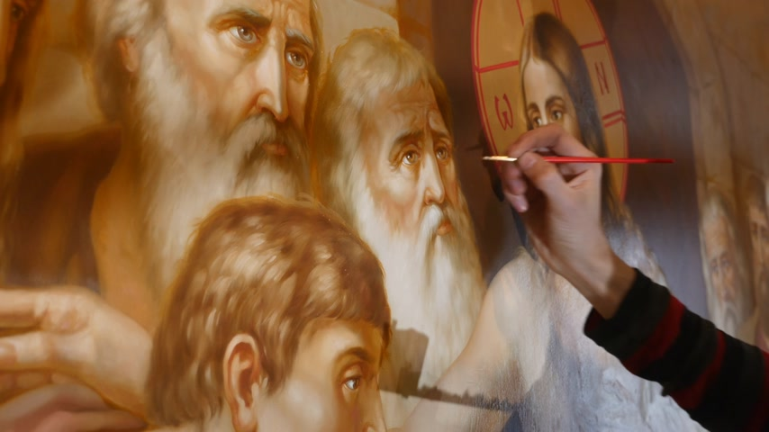 30.01.2018, Chernivtsi, Ukraine - Man`s Artist hand is Standing and painting the Icon of Orthodox Saint , Holding a Palette With Paints