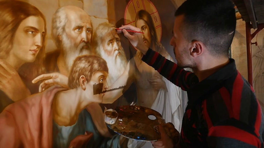 restauração : 30.01.2018, Chernivtsi, Ukraine - Male Artist is Standing and painting the Icon of Orthodox Saint , Holding a Palette With Paints