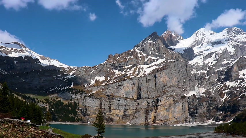 tampado : Lake Oeschinen with snowy mountains and clouds - time lapse