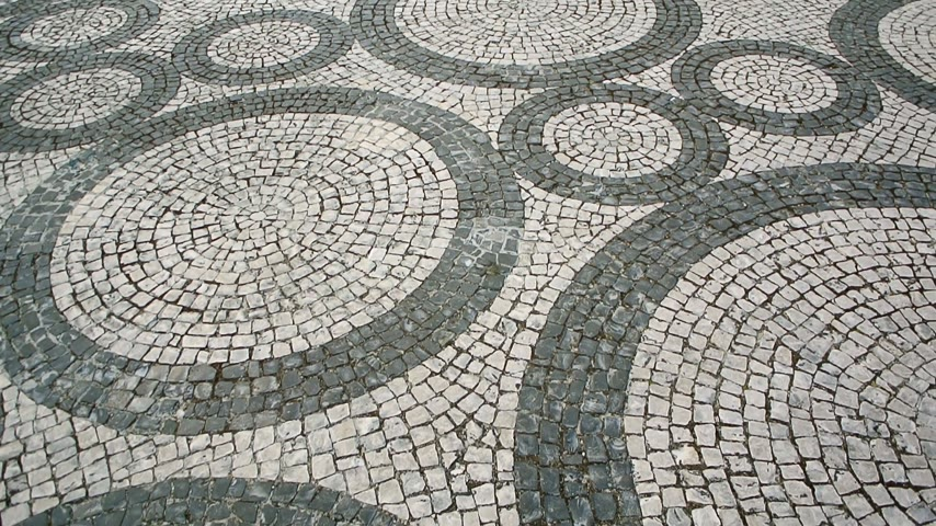 kamień : Typical Portuguese black and white stone mosaic calcada pavement - seen in all the Portugal - Cascais, Lisbon, Guimaraes. Also can be seen in Rio de Janeiro, Brazil.