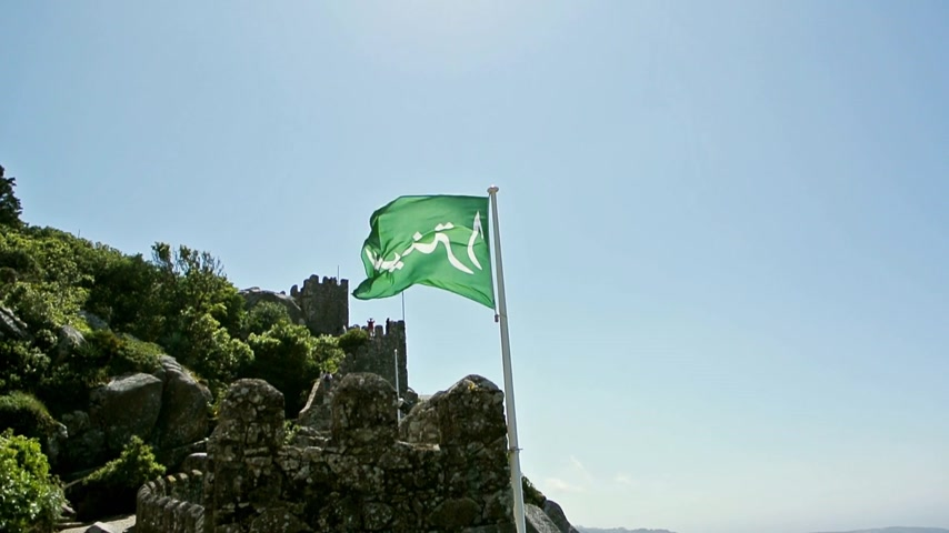средневековый : Green flag waving in the wind over the Moorish Castle with an inscription in arabic language of the word Sintra