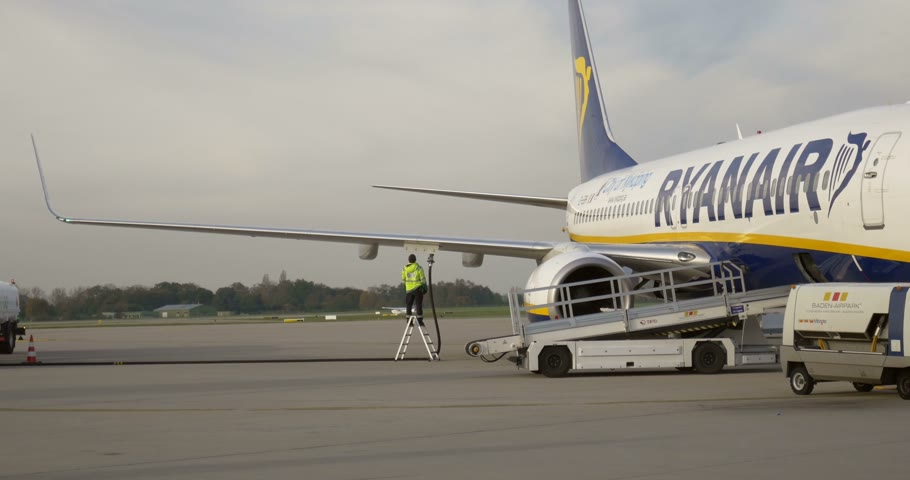 fosilní : BADEN-BADEN, GERMANY - OCTOBER 24, 2014: Airport technical crew loading fuel into passenger airplane jet which belongs to the low-cost RyanAir as seen on Baden Airport