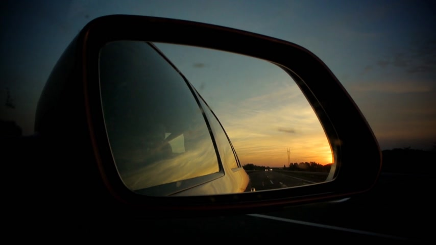 városi : Car driving with vivid sunset (sun going down) in read side mirror. Other cars are reflected as well as the trees and bridges Stock mozgókép