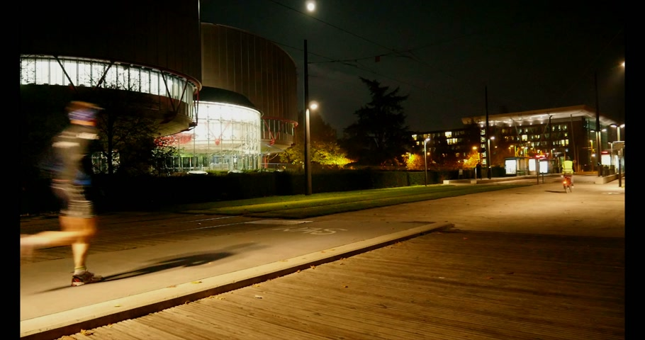 coe : STRASBOURG, FRANCE - NOVEMBER 6, 2014:  Headquarters of European Court of Human Rights - ECHR - with runners, cyclist, and walking  man passing in front of the building at night.  ECHR is a international court established by the European Convention on Hum