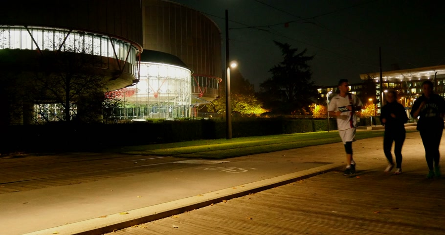 coe : STRASBOURG, FRANCE - NOVEMBER 6, 2014:  Headquarters of European Court of Human Rights - ECHR - with a three runners passing in front of the building at night.  ECHR is a international court established by the European Convention on Human Rights. Stock Footage