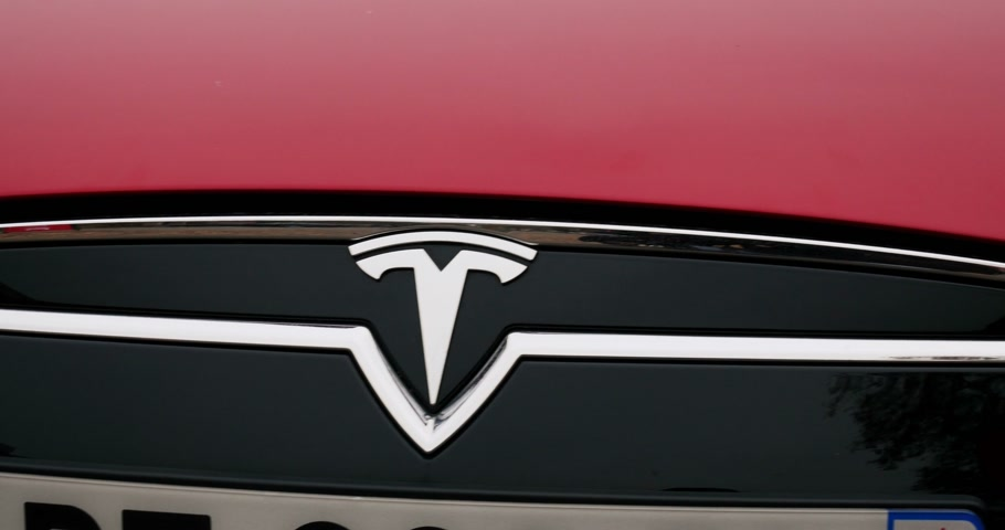 tesla model s : PARIS, FRANCE - 28 NOVEMBER 2014: Panning over red color Tesla Model S 85 headlight to the stylized Tesla frontal insignia. Tesla Motors, Inc. is an American company that designs, manufactures, and sells electric cars and electric vehicle powertrain compo Stock Footage