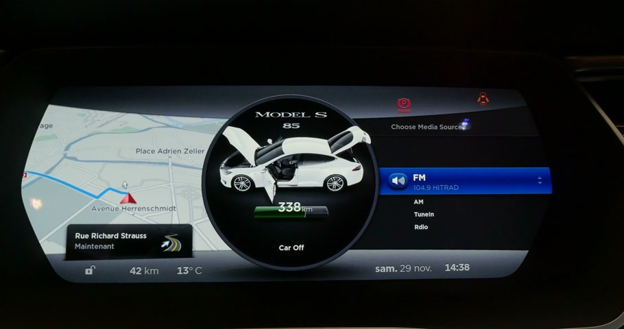 tesla model s : PARIS, FRANCE - 28 NOVEMBER 2014: Detail of the Tesla Model S digital dashboard indicating autonomy for more than 338 km and digital selection of music station and volume levels. Tesla Motors, Inc. is an American company that designs, manufactures, and se