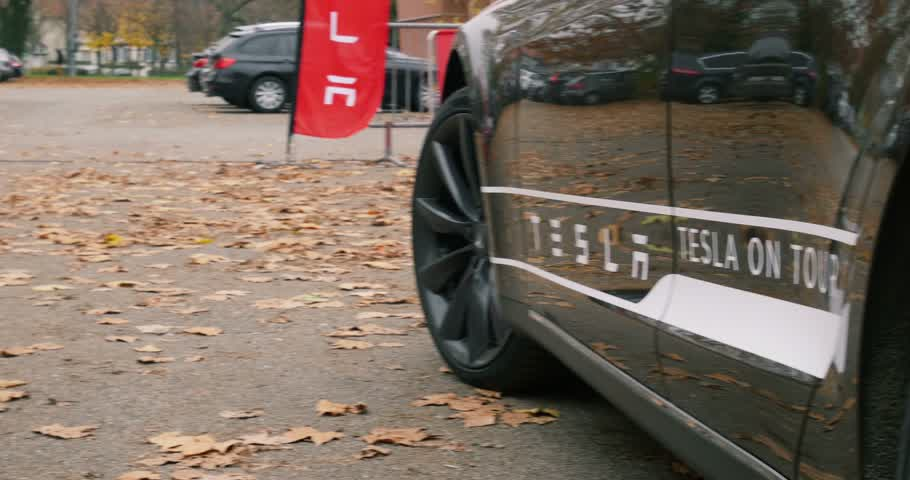 tesla model s : PARIS, FRANCE - 28 NOVEMBER 2014: Panning over two Tesla electric cars. Tesla Motors, Inc. is an American company that designs, manufactures, and sells electric cars and electric vehicle powertrain components Stock Footage