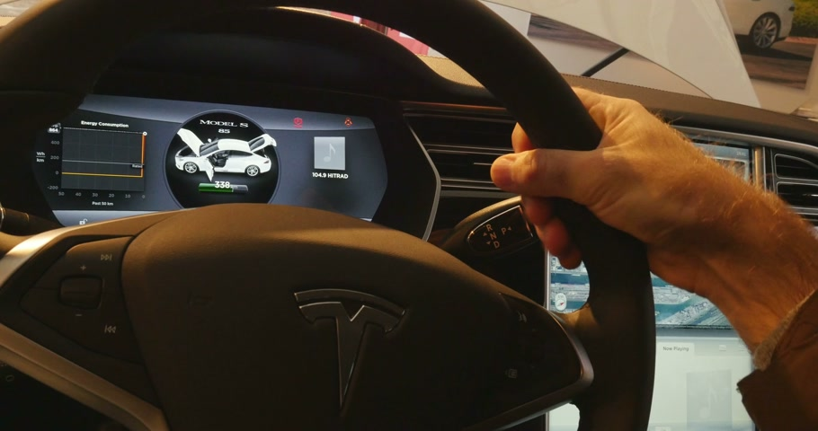 tesla model s : PARIS, FRANCE - 28 NOVEMBER 2014: Man testing steering wheel of a Tesla Electric Car with digital dashboard indicating autonomy for more than 338 km. Tesla Motors, Inc. is an American company that designs, manufactures, and sells electric cars and electri