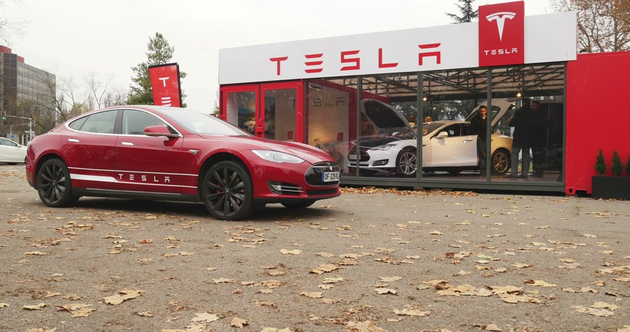 tesla model s : PARIS, FRANCE - 28 NOVEMBER 2014: Tesla Motors showroom with customers and managers presenting car. Tesla Motors, Inc. is an American company that designs, manufactures, and sells electric cars and electric vehicle powertrain components