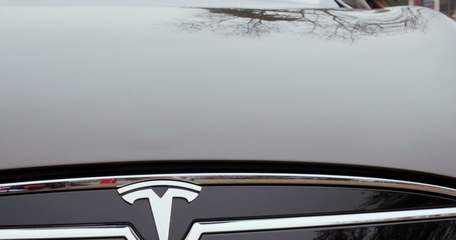 tesla model s : PARIS, FRANCE - 28 NOVEMBER 2014: Panning down to brown color Tesla Model S 85 frontal insignia. Tesla Motors, Inc. is an American company that designs, manufactures, and sells electric cars and electric vehicle powertrain components