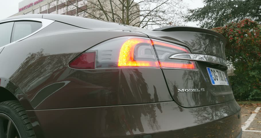 tesla model s : PARIS, FRANCE - 28 NOVEMBER 2014: Man admiring new Tesla Model S 85 electric vehicle leaving the parking for a test drive. Tesla Motors, Inc. is an American company that designs, manufactures, and sells electric cars and electric vehicle powertrain compon