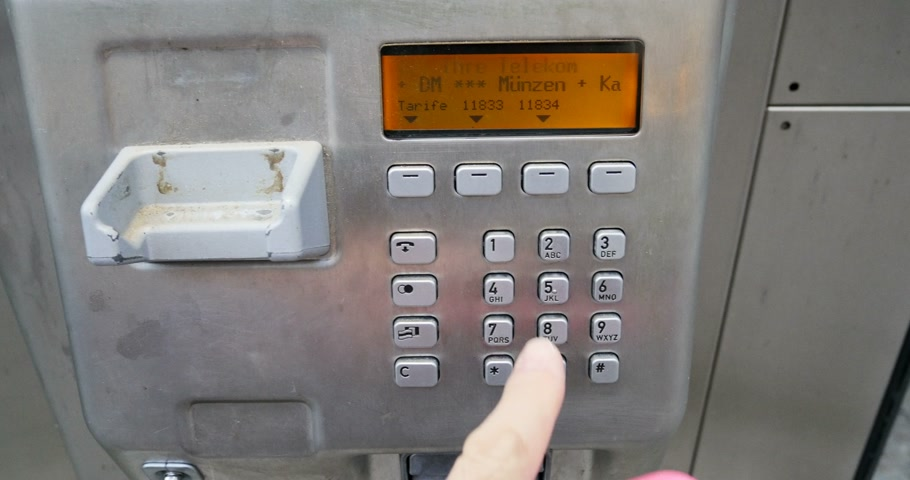 almanca : BADEN-BADEN, GERMANY - DECEMBER 10, 2014: Hand dialing phone number on a  Deutsche Telekom - German telecom public telephone keyboard with digital display. Deutsche Telekom AG (abbreviated DTAG, English: German Telecom) is a German telecommunications comp