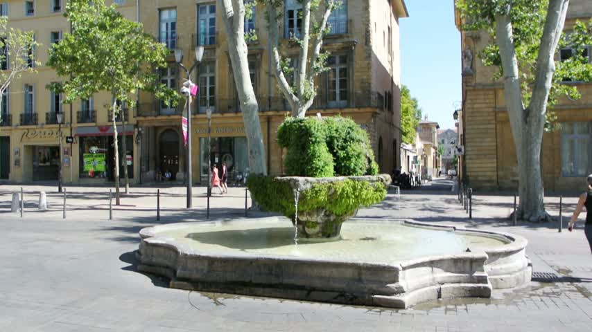 neuf : AIX-EN-PROVENCE, FRANCE - JULY 22, 2014: View of Cours Mirabeau street in the center of the city with the beautiful Fontaine des Neuf-Canons. fountain, cars and pedestrians