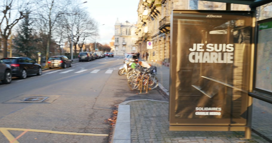 mourners : STRASBOURG,, FRANCE - 11 JAN, 2015: Bus stop with large Je Suis Charlie seen in French city after the unity rally (Marche Republicaine) where some 50000 people took part in tribute three-day killing spree in Paris
