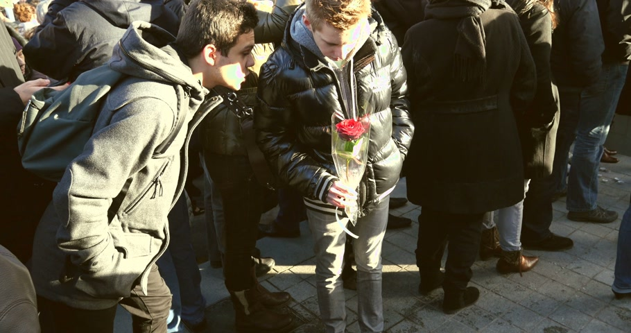 mourners : STRASBOURG, FRANCE - 11 JAN, 2015: Young boy posing flowers at Charlie Hebdo hommage place in Strasbourg where some 50000 people took part in tribute three-day killing spree in Paris at Charlie Hebdo satirical magazine  Stock Footage
