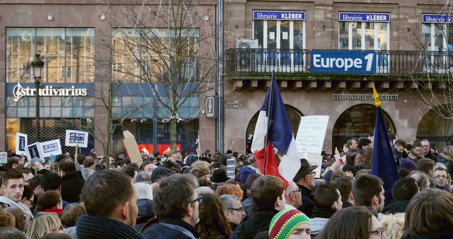 je suis charlie : STRASBOURG, FRANCE - 11 JAN, 2015: French national Flag at Place Kleber during a unity rally (Marche Republicaine) where some 50000 people took part in tribute three-day killing spree in Paris - lens flare Stock Footage