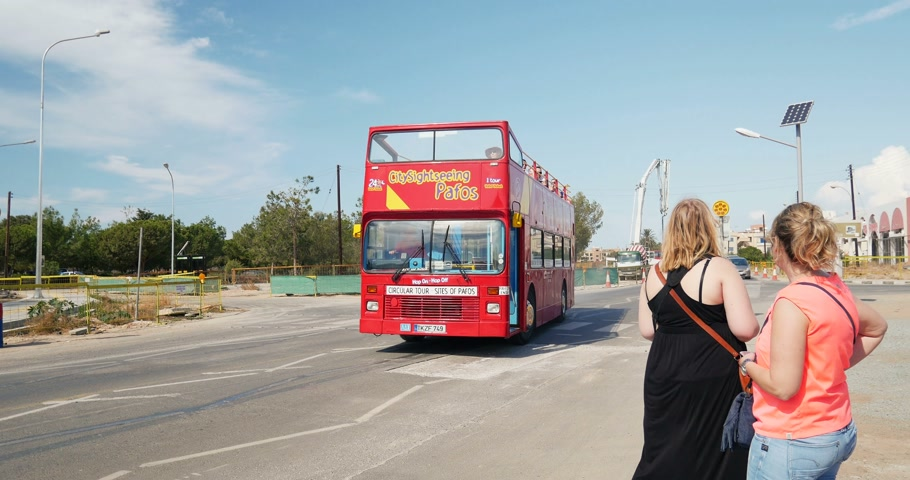 vyhlídkové : PAPHOS, CYPRUS - 15 OCT 2014: Hop-On Hop-Off Tours sightseeing tourist red bus passing in front of two tourists on a sunny day. Shot on UHD 4K Production Digital Camera - easy to crop and edit