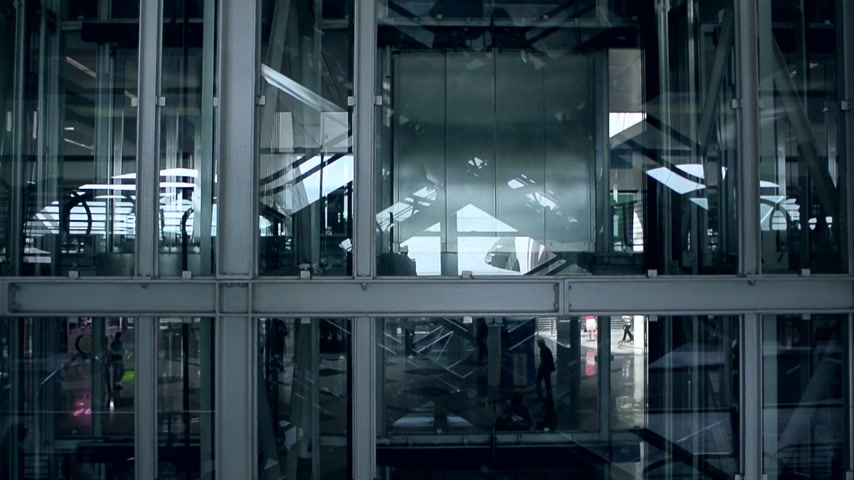 лифт : Modern airport transportation hub with silhouettes descending and ascending on escalator - reflection in windows