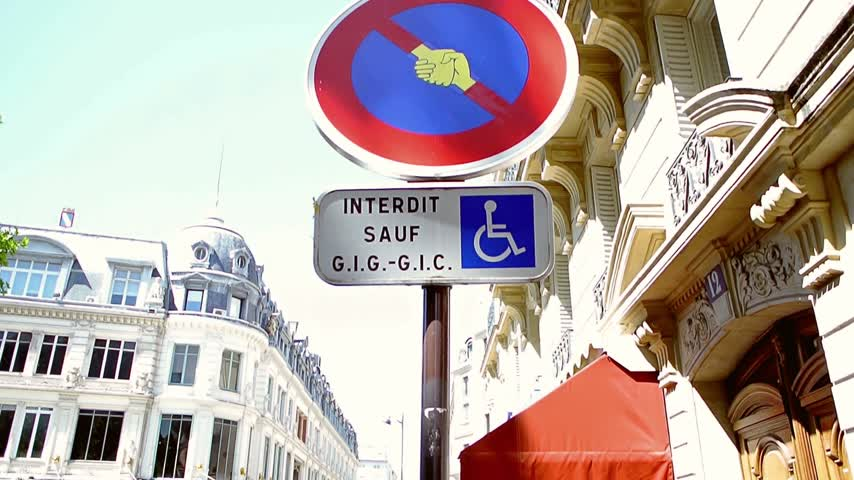 interdiction : PARIS, FRANCE - CIRCA 2015: Panning over altered with shaking hands street transportation sign
