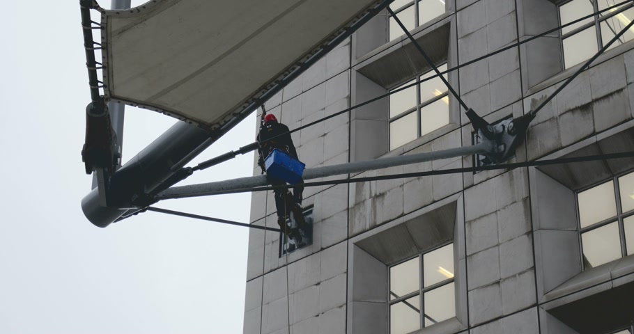 arche : Window cleaning worker hanging with ropes and swinging on the high floor of La Defense, Grande Arche, Paris shot with a telephoto lens zoom.