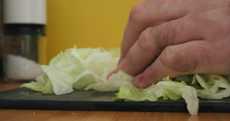 marul : Mans hands chopping slicing up fresh  lettuce (Lactuca sativa) leaf salad leaves in kitchen, close-up