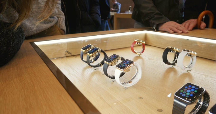 admirado : PARIS, FRANCE – APR 10, 2015: New wearable computer Apple Watch smartwatch Edition gold collection being admired by customers and fans. Apple Watch incorporates fitness tracking and health-oriented capabilities and  integration with iOS Apple products and