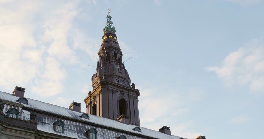 birleşik : Steeple on top of Christiansborg Palace or Christiansborg Castle (Danish: Christiansborg Slot) on the islet of Slotsholmen in central Copenhagen, is the seat of the Danish Parliament (Folketinget), the Prime Ministers Office and the Supreme Court. Also,  Stok Video
