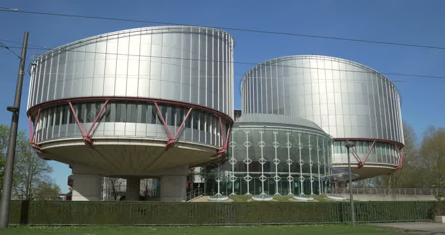 european court of human rights : STRASBOURG FRANCE  CIRCA 2015: Cyclist biker passing in front of the European Court of Human Rights ECtHR or Cour europeenne des droits de lhomme  in Strasbourg  Alsace Eurometropole France on a sunny day with blue sky Stock Footage