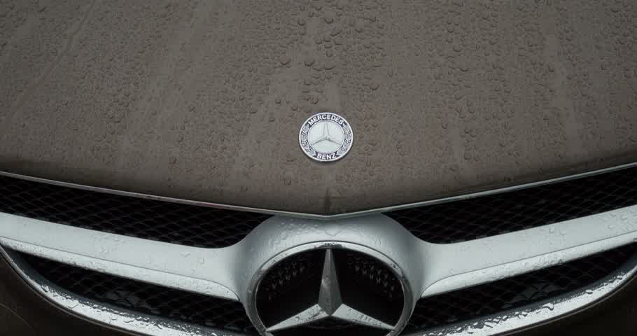 embléma : STUTTGART GERMANY  CIRCA 2015: Mercedes Benz Sign slowmotion closeup over a sport car. MercedesBenz is a German automobile manufacturer a multinational division of the German manufacturer Daimler AG. The brand is used for luxury automobiles buses coaches  Stock mozgókép