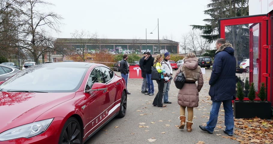 tesla model s : PARIS FRANCE  CIRCA 2015: People buying hybrid Tesla Model S electric car at  showroom. Tesla is an American company that designs manufactures and sells electric cars