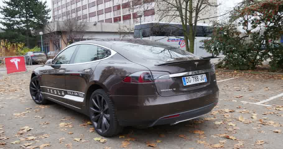 tesla model s : PARIS FRANCE  CIRCA 2015: Panning to metallic grey Tesla Model S at  showroom. Tesla is an American company that designs manufactures and sells electric cars