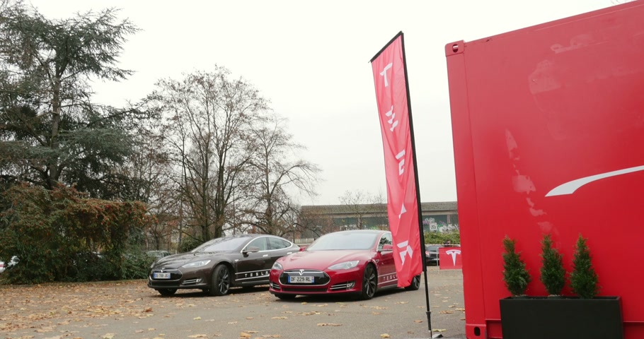 tesla model s : PARIS FRANCE  CIRCA 2015: Tiltdown to Tesla showroom with red and gray electric Tesla Modesl S cars. Tesla is an American company that designs manufactures and sells electric cars
