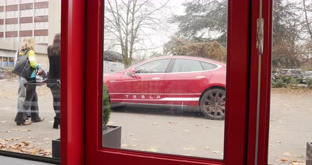 model s : PARIS FRANCE  CIRCA 2015: View from the card dealer showroom to the exterior car with customer deciding before buying the new Tesla Modesl S car. Tesla is an American company that designs manufactures and sells electric cars